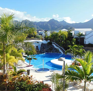 Large swimming pool set in the middle of a holiday resort. Surrounded by pristine white accommodation, lush gardens and towering mountains.