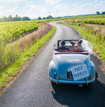 Newlyweds drive along an open country road in a traditional wedding car with 'just married' sign.