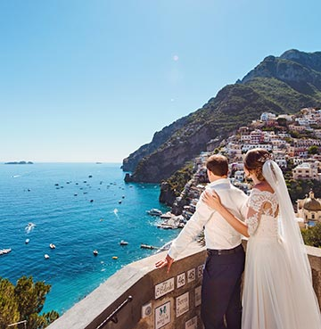 Newlywed Bride and Groom look out over the picture-perfect Amalfi Coast from an ornate balcony