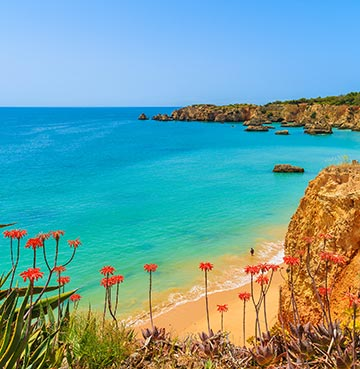 View over turquoise waters, golden sands and towering cliffs on the Algarve coastline from the Pine Cliffs Resort