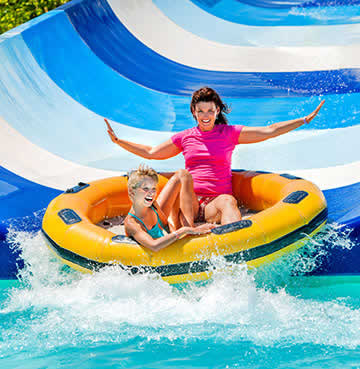 Mother and son on a rubber ring, shooting down a waterside at the water park