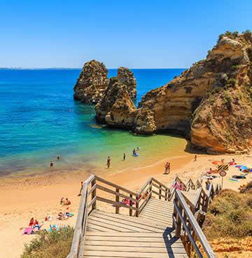 Wooden boardwalk down to a golden beach nestled between the cliffs