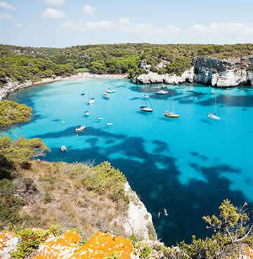 Sapphire blue waters and lush green pines at Cala Macarelleta, Menorca