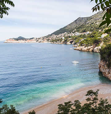 The secluded Sveti Jakov Beach, with Dubrovnik's Old Town in the background