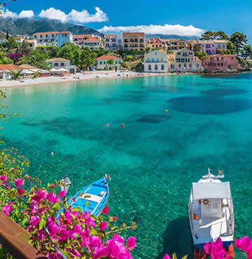 Picturesque Assos village boasting aquamarine bay waters, bright pink florals and pastel coloured houses