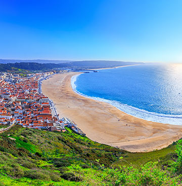 The wild waters of Nazaré beach, Portugal are perfect for surfing along the Silver Coast