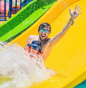 Father and son on a water slide at a water park