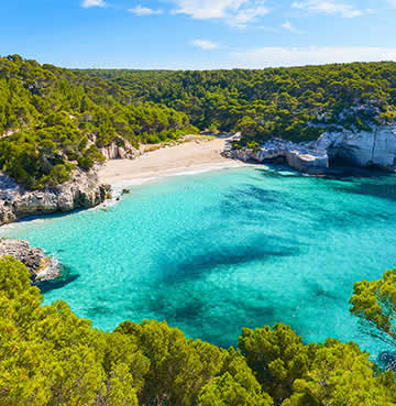 Secluded beach in Menorca surrounded by luscious vegetation and azure waters of the Mediterranean Sea