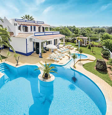 Whitewashed villa with landscaped gardens and a large swimming pool