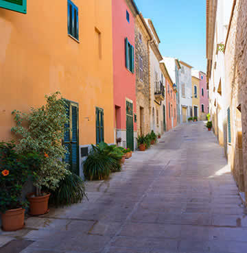 Candy-coloured residences line cobbled streets in Alcudia
