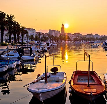 Riva Promenade lined with palm trees and bobbing boats at sunset