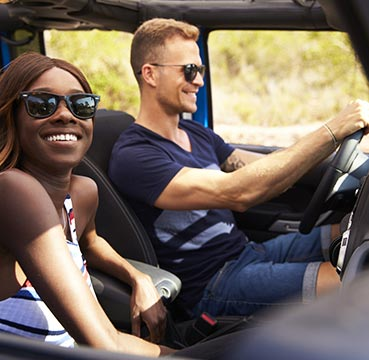 A young couple driving in a hire car