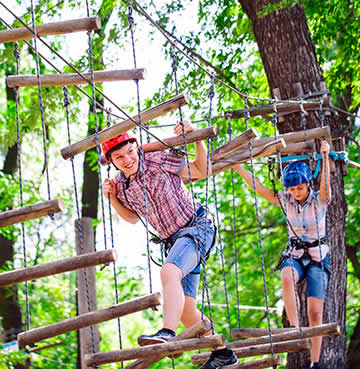 Two young children make their way across a rope assault course in tree tops in the Algarve