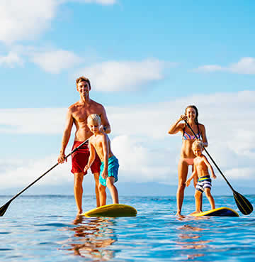 A young family stand up paddle boarding in Mallorca