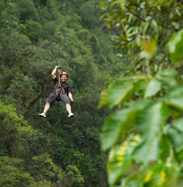A man wearing a red helmet and safety harness ziplines through the rainforest in Antigua