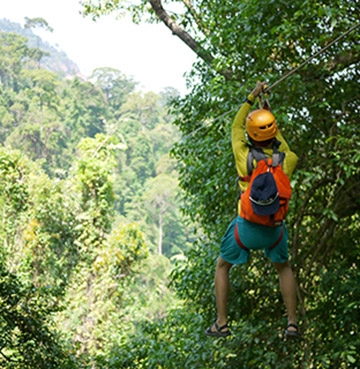 A young child wearing a safety helmet ziplines through the rainforest canopy in Dominican Republic