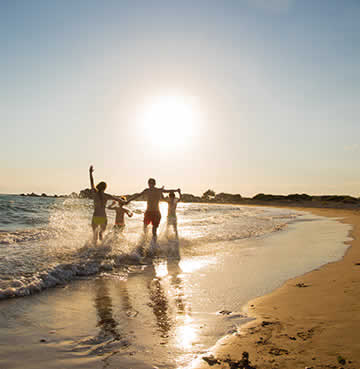 Young family playing in the shallow waves on a golden, sandy beach at sunset