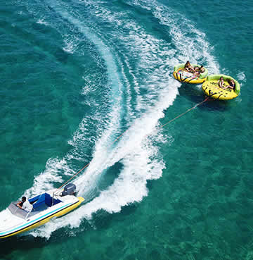 Family water fun on inflatables being pulled across azure seas by a speedboat