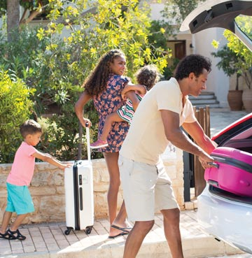 Family unloading luggage from the hire car outside villa