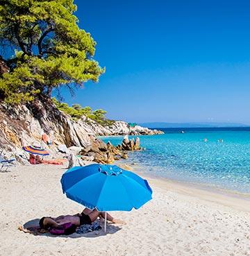 Blue beach umbrella on the golden sand