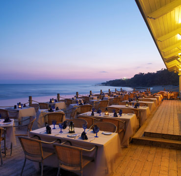 A beach side restaurant at sunset. Candle lit tables are laid out perfectly waiting for guests to arrive.