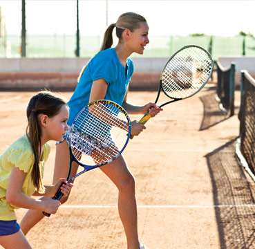 Mum and daughter stand side by side on a tennis court, practicing their techniques and stance