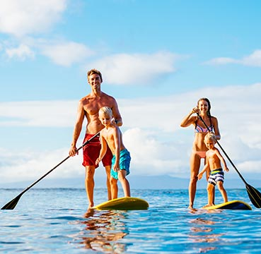 A young family stand up paddle boarding together in perfect blue waters