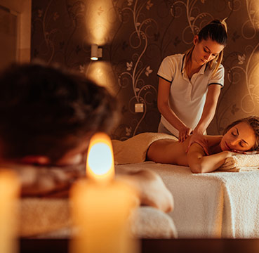 A young man and woman indulging in a couple's massage. The room has aromatic candles and dimmed lighting to add to the relaxing experience.