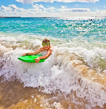 A young boy on a green surf board rides the waves in Lanzarote