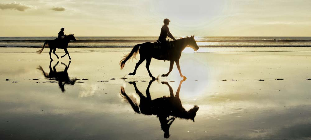 2 people horseriding on a beach at sunset
