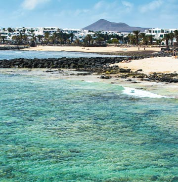 Crystal clear turquoise waters, golden sands and rocky headlands at Playa las Cucharas