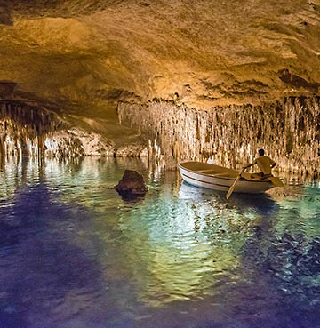 A man rowing his boat in the underground cave system of Cuevas del Drach