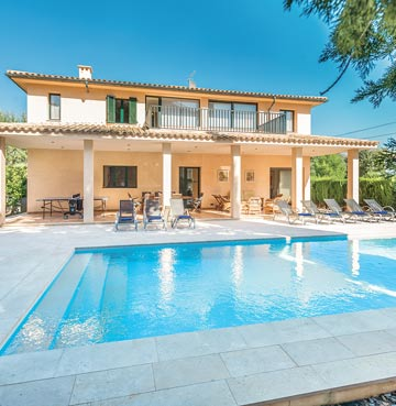 A modern, luxury villa with large swimming pool. Sunloungers and dining facilities are set up around the terrace area