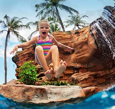 Young girl jumping into a beautiful swimming pool with waterfall