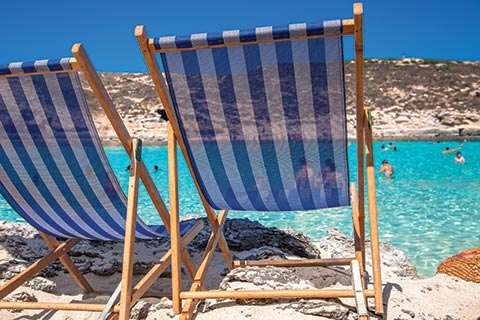 Two blue and white striped deck chairs overlooking a blue lagoon