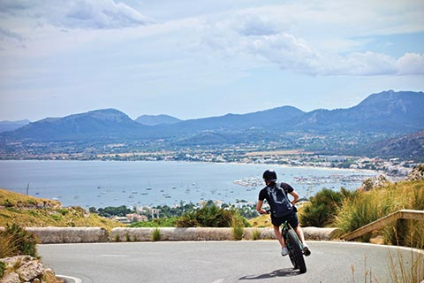 A Male cyclist turns round the corner of a coastal highway, with vistas over the bay and mountains