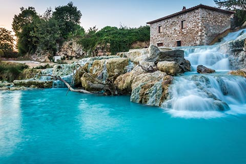 Waters cascade down rocks at the Saturnia Thermal Spring in Tuscany