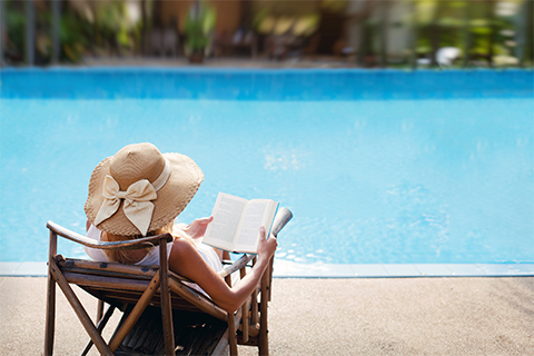 A woman reading a book by the pool on holiday