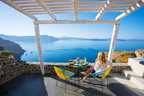 A young woman enjoying breakfast overlooking the iconic Caldera in Santorini