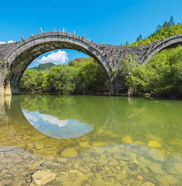 A unique circular bridge straddles a picturesque river