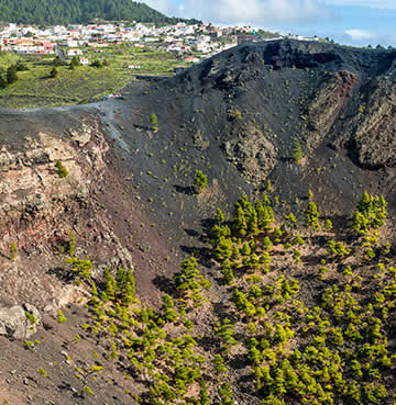 Dark sands and red-hued cliffs of a volcanic crater in Tenerife.