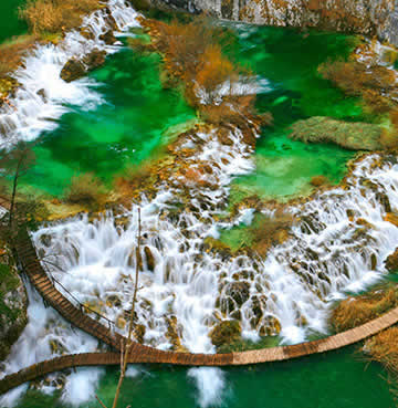 An aerial view of Croatia's Plitvice National Park. The lake is a vivid green, with water flowing through the limestone rocks.