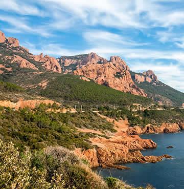 Red-hued mountains bursting with greenery stretches out across the Mediterranean sea in Provence.