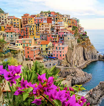 A cluster of colourful houses carved into the cliff face as they overlook the Mediterranean Sea in Italy's Cinque Terre.