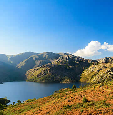 Peak dark green valleys and mountains overlooking azure waters at Portugal's Peneda-Gerês