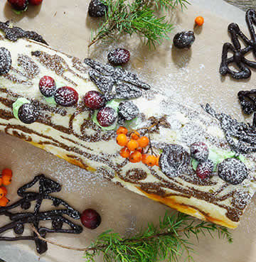 Birds-eye-view of a Buche de Noel. Decorated with chocolate icing and seasonal berries.