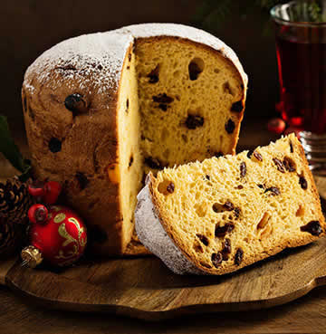 Italian panettone displayed beautifully with pine cones and Christmas baubles. A glass of warm mulled wine sits in the background.
