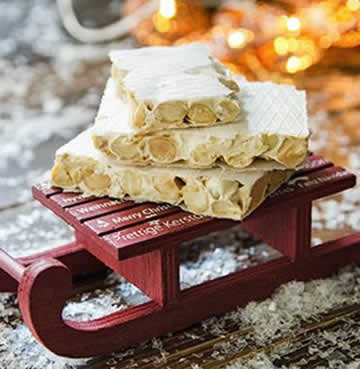 Turron de Navidad stacked on a little Christmas sleigh with Christmas lights in the background