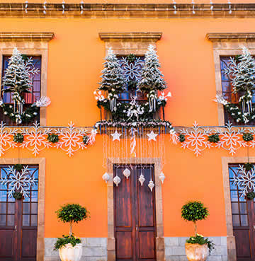 Festive decorations displayed on a traditional terracotta house in Spain.