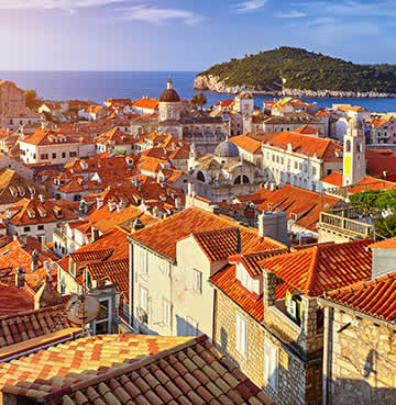 Fortified walls and red-roofed buldings in Dubrovnik Old Town, lapped by the Adriatic Sea.